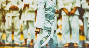 Karat? do conceito, artes marciais Conceito da lideran?a, vit?ria, artes marciais O lutador executa exerc?cios na frente da fotografia de stock