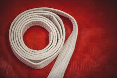 Karate άσπρη ζώνη στο κόκκινο υπόβαθρο στοκ εικόνες