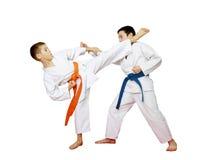Karate αθλητών εκπαιδεύει τις ταξινομημένες κατά ζεύγος ασκήσεις σε ένα άσπρο υπόβαθρο Στοκ Φωτογραφία