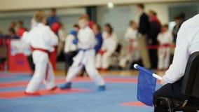 Karate ανταγωνισμών πολεμικής τέχνης - ο δικαστής προγυμνάζει την εξέταση τη θηλυκή karate εφήβων ` s πάλη απόθεμα βίντεο