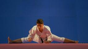 Karate ατόμων συνεδρίαση επαγγελματιών στη θέση σπάγγου στο πάτωμα τεντώνοντας τους μυς του κατά τη διάρκεια της προθέρμανσης απόθεμα βίντεο