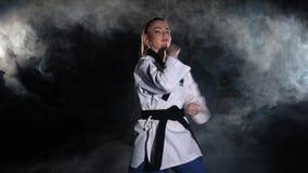 Karate κορίτσι λακτίσματος στους τεχνικούς πυροβολισμούς πρακτικής κιμονό μαύρα απόθεμα βίντεο