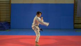 Karate μαύρος επαγγελματίας ζωνών ατόμων που εκτελεί το kata στο dojo απόθεμα βίντεο