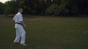 Karate ο κύριος στην πάλη σκιών πρακτικών κιμονό, κάνει μια σειρά λακτισμάτων και τα λακτίσματα, εκπαιδεύουν το πρωί στην πόλη φιλμ μικρού μήκους
