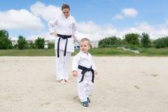 Karate παιδί - πορτρέτο του μικρού παιδιού στο κιμονό Η μητέρα αγοριών ` s είναι σε ένα κιμονό σε ένα υπόβαθρο Στοκ φωτογραφία με δικαίωμα ελεύθερης χρήσης
