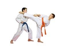 Karate τεχνικής εκτελεί μέσα τους αθλητές με την πορτοκαλιά και μπλε ζώνη Στοκ Εικόνα
