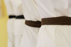 Karate. Close up of people lining up during karate practise, focus on the first belt stock photos