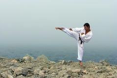Karate bildet auf den Ufern des Meeres aus Stockbild