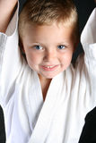 Karate Boy. Young boy wearing his karate uniform on a black background royalty free stock photography