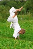 Karate boy does handstand on lawn Royalty Free Stock Photos