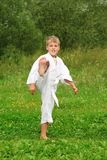Karate boy kick a leg outdoor Stock Photos