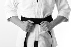 Karate boy. Male torso and sportive arms on white background. Guy poses in white kimono with black belt, close up Royalty Free Stock Photography