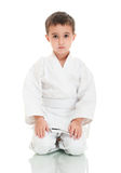 Karate boy sitting in white kimono Stock Photography