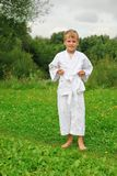 Karate boy stands on lawn Stock Photography