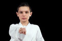 Karate boy in white kimono fighting isolated on black  background Stock Image