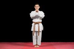 Karate boy in white kimono fighting isolated on black  background Royalty Free Stock Photo