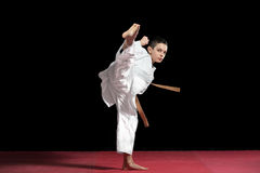 Karate boy in white kimono fighting isolated on black  background Royalty Free Stock Photography