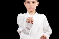 Karate boy in white kimono fighting isolated on black  background Stock Photo