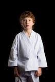 Karate boy in white kimono isolated on black Stock Image