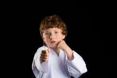 Karate boy in white kimono isolated on black Stock Photos