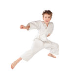 Karate boy in white kimono jumping isolated Stock Photography