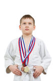 Karate boy in white kimono with medals fighting Royalty Free Stock Images