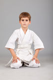 Karate boy in white kimono is sitting Royalty Free Stock Images