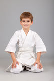 Karate boy in white kimono is sitting Stock Photography