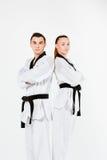 Karate chłopiec z czarnymi paskami i dziewczyna Obrazy Royalty Free