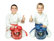 Karate children sit in a ritual pose with helmets and point the finger isolated Stock Image