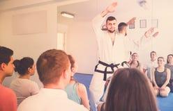 Karate coach teaching adults Stock Photos