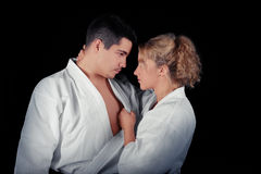 Karate Couple Passion. Young passionate couple wearing kimonos on a black background Stock Photo