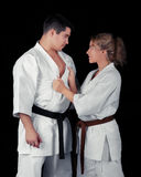 Karate Couple Passion. Young passionate couple wearing kimonos on a black background Royalty Free Stock Images