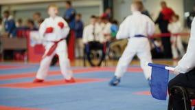 karate De-enfocado de las competencias del arte marcial - juzgue a los coches que miran la lucha femenina del karate del ` s del  Foto de archivo