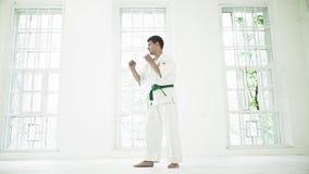 Karate de entrenamiento del hombre sobre el fondo blanco de las ventanas almacen de metraje de vídeo
