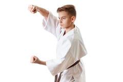 Karate del deporte del arte marcial - muchacho adolescente del niño en el sacador y el bloque blancos del entrenamiento del kimon Imagenes de archivo