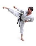 Karate. El hombre en un kimono golpea el pie Imagen de archivo libre de regalías