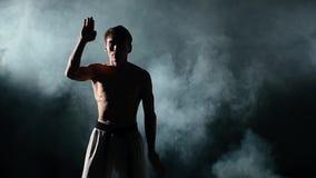 Karate- eller Taekwondo man med en naket torso och a lager videofilmer