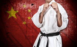 Karate fighter in kimono and china flag Stock Photos