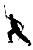 Karate fighter with sticks. Black silhouetted karate fighter with two long sticks in combat stance, white background Royalty Free Stock Images