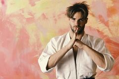 Karate fighter with strong body shows traditional martial arts greeting. Japanese karate concept. Guy poses in white. Kimono. Man with confident face and stock images