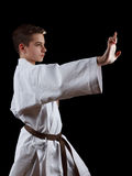 Karate Fighter in white Kimono Isolated on Black Stock Image