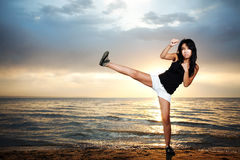 Karate girl on the beach. Cute asian girl stay on the beach and kick Stock Photo