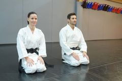 Karate girl and boy with black belts Royalty Free Stock Image