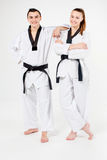 The karate girl and boy with black belts Royalty Free Stock Photos