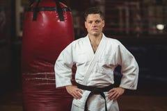 Karate gracz stoi w sprawności fizycznej studiu z rękami na biodrach fotografia stock