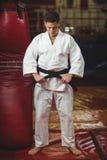Karate gracz wiąże jego pasowego fotografia stock