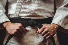 Karate gracz wiąże jego pasowego Zdjęcia Stock