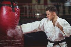 Karate gracza ćwiczy karate z uderzać pięścią torbę zdjęcie stock