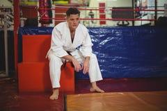 Karate gracza obsiadanie w sprawności fizycznej studiu zdjęcie royalty free